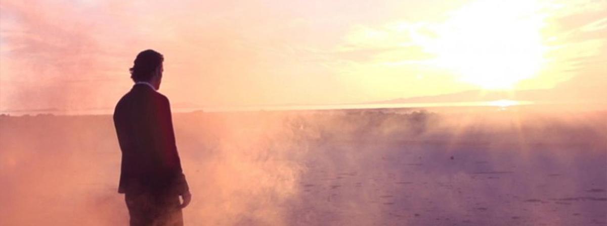 Ein Mann in einem Anzug blickt zur untergehenden Sonne