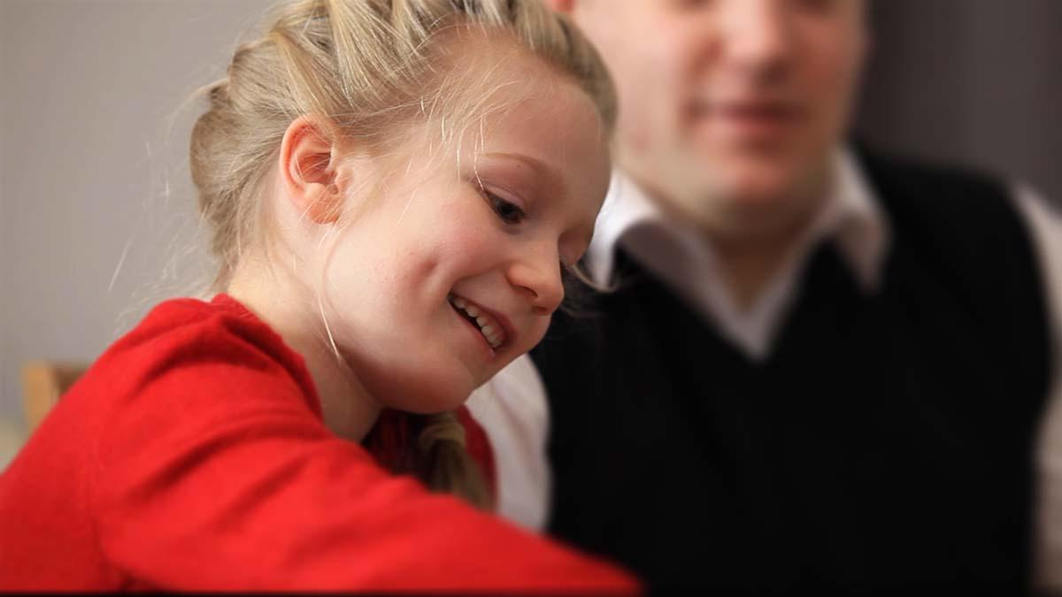 Fillette souriante jouant aux cartes avec sa famille.