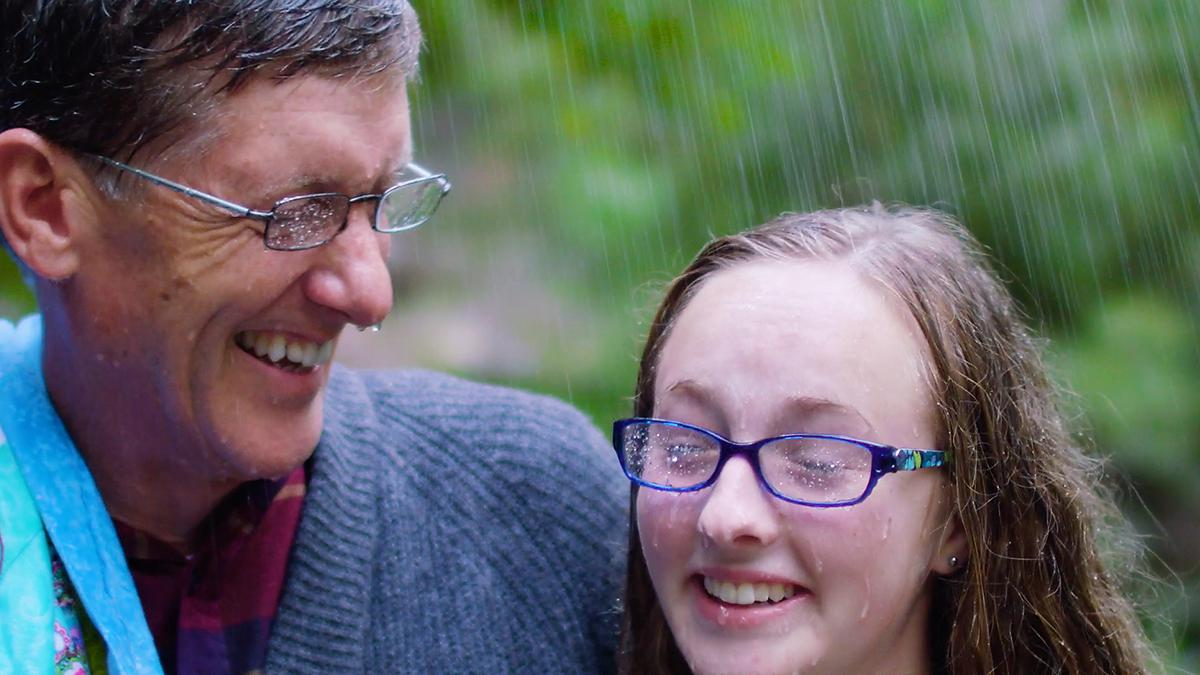 A man and his Granddaughter are laughing together in the rain.