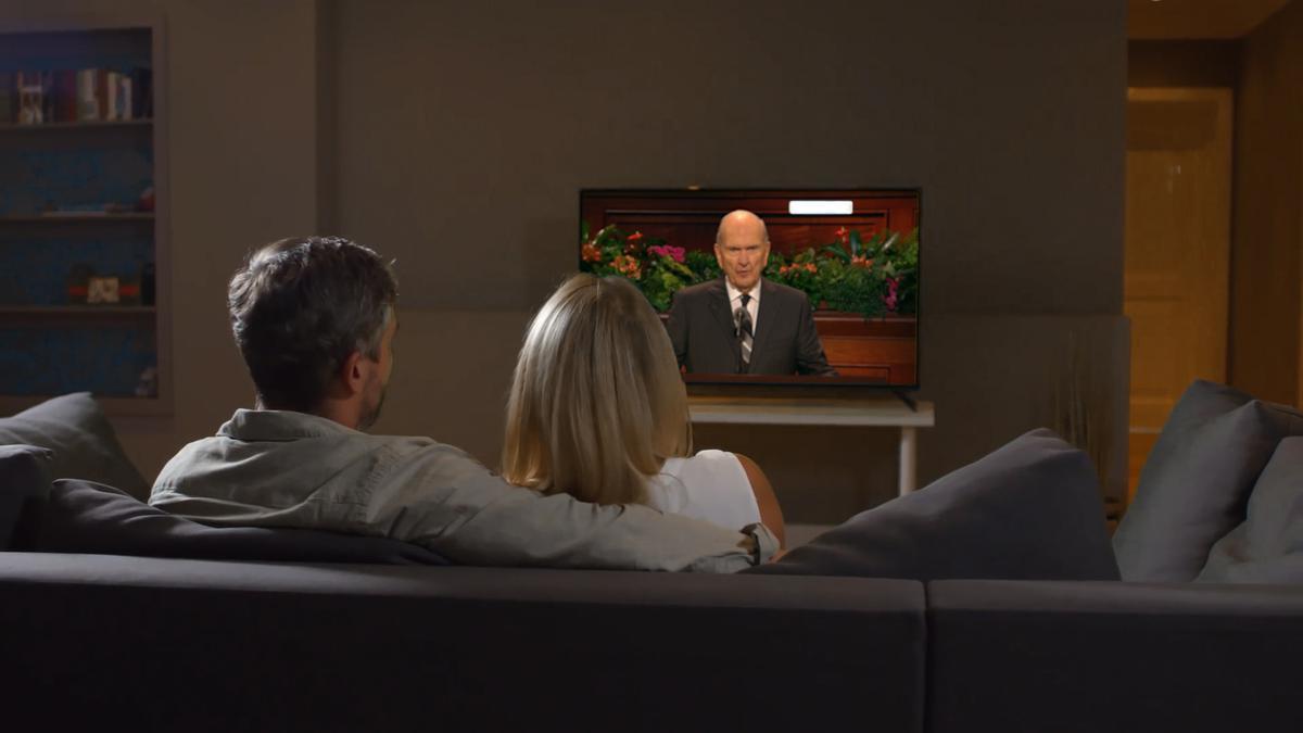 Una pareja sentada ve al profeta hablar por televisión.