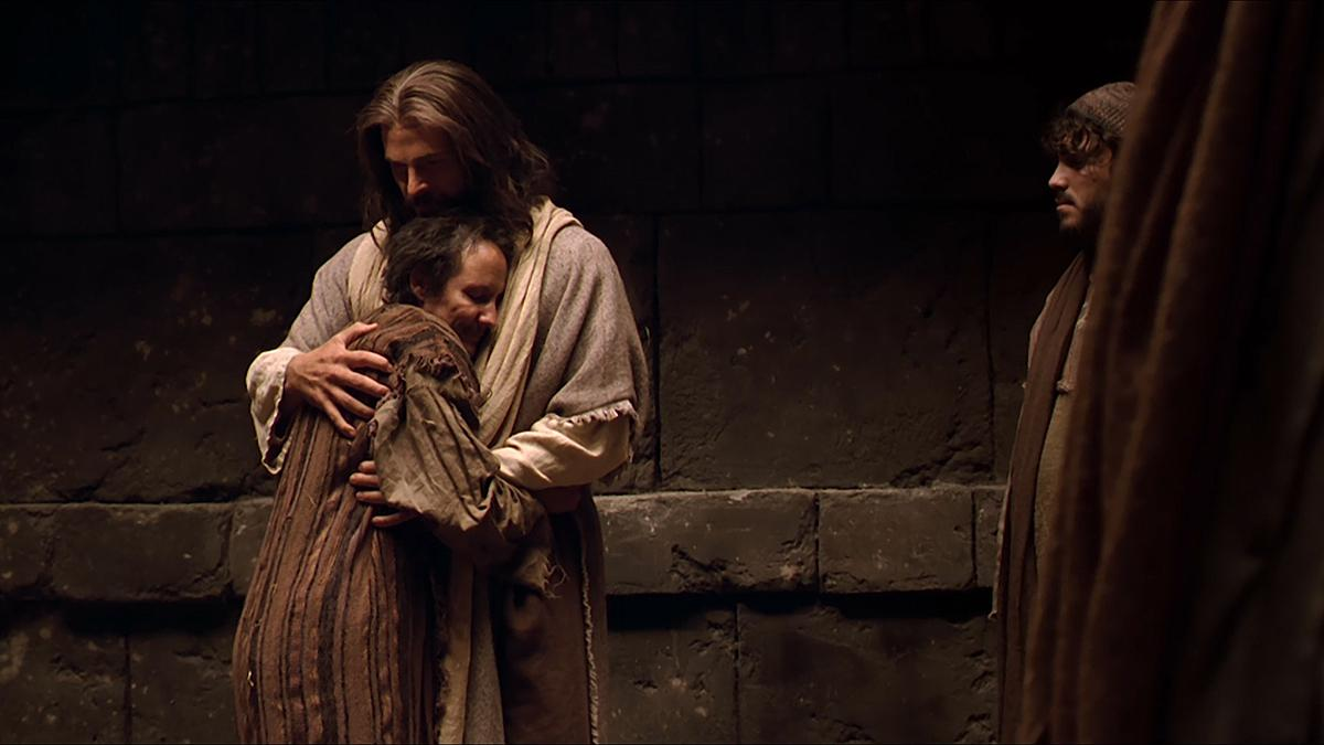 Jesus embraces a man.