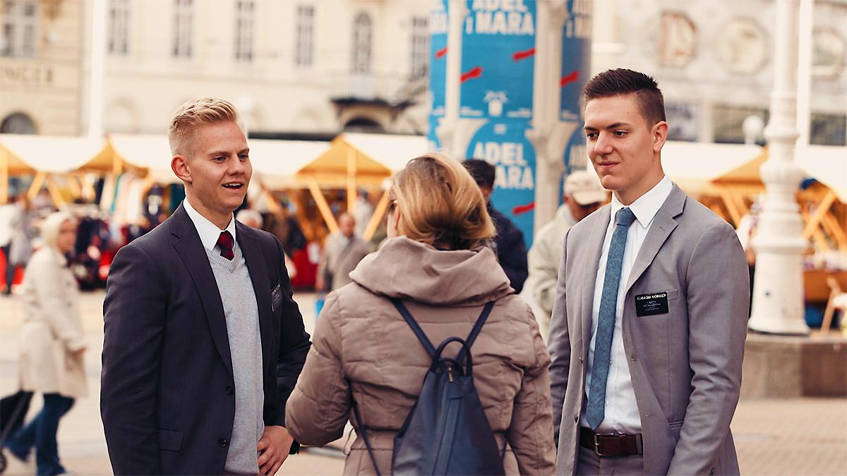 Two missionaries share the Gospel on the streets.