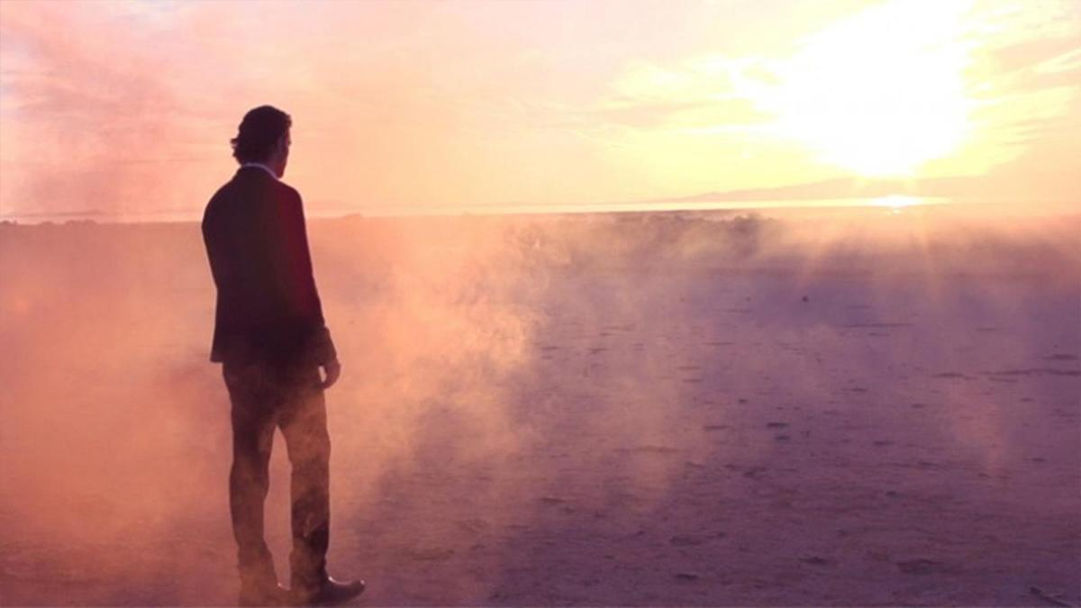 Muž vobleku se dívá na západ slunce