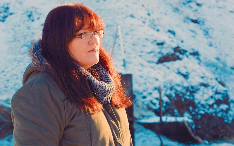 En kvinde ser længselsfuldt ud i horisonten.