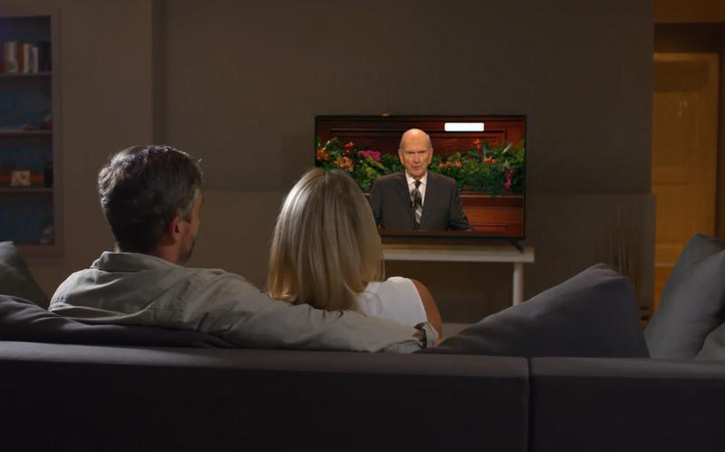 Um casal sentado a assistir, na televisão, ao profeta a falar.