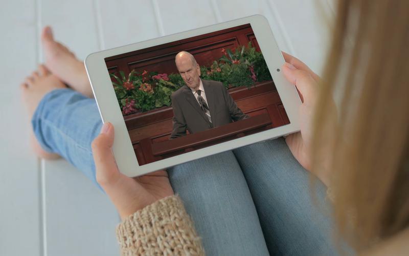 Jeune femme regardant sur sa tablette le prophète faire un discours