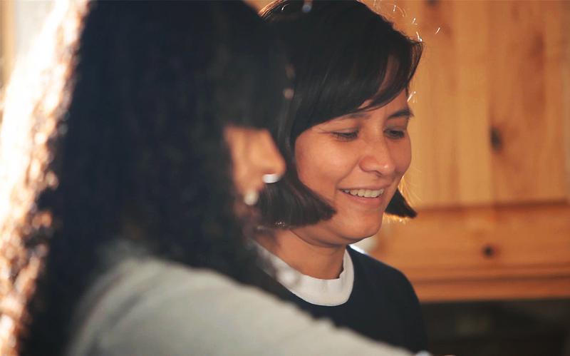 Una madre sonríe con su hija en la cocina.