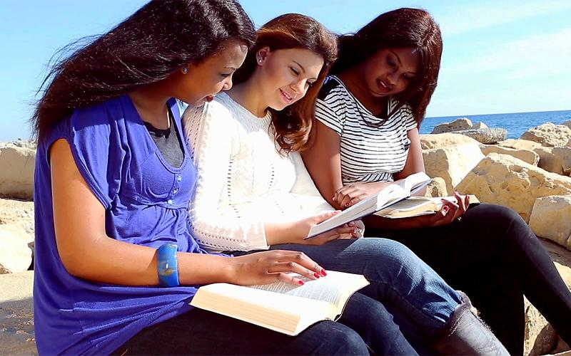 Tri dekleta sedijo ob morju in berejo svete spise.