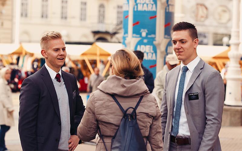 Dos misioneros comparten el Evangelio en la calle.
