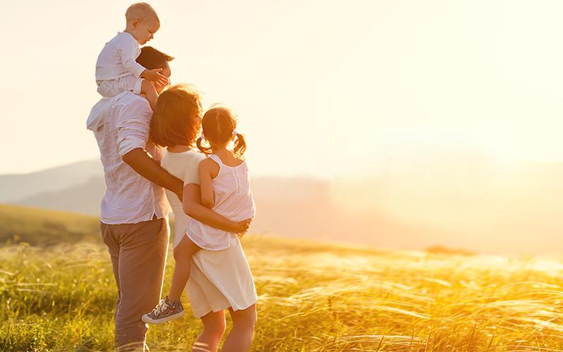 Fotografia e një familjeje të lumtur në një fushë.