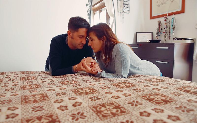 Una pareja orando junto a su cama