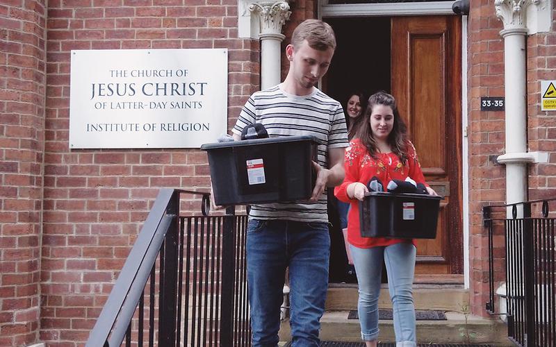 En gruppe unge voksne bærer på kasser