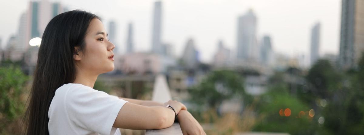 En ung pige ser på himlen over byen.