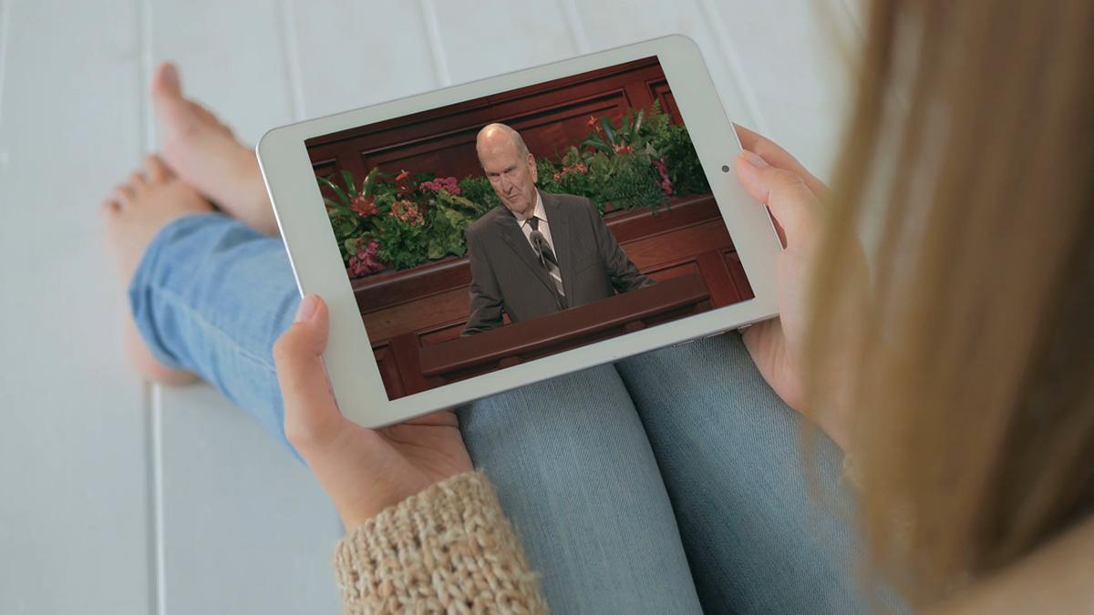 Tânără care s-a așezat și care-și folosește tableta pentru a-l viziona pe profet vorbind.