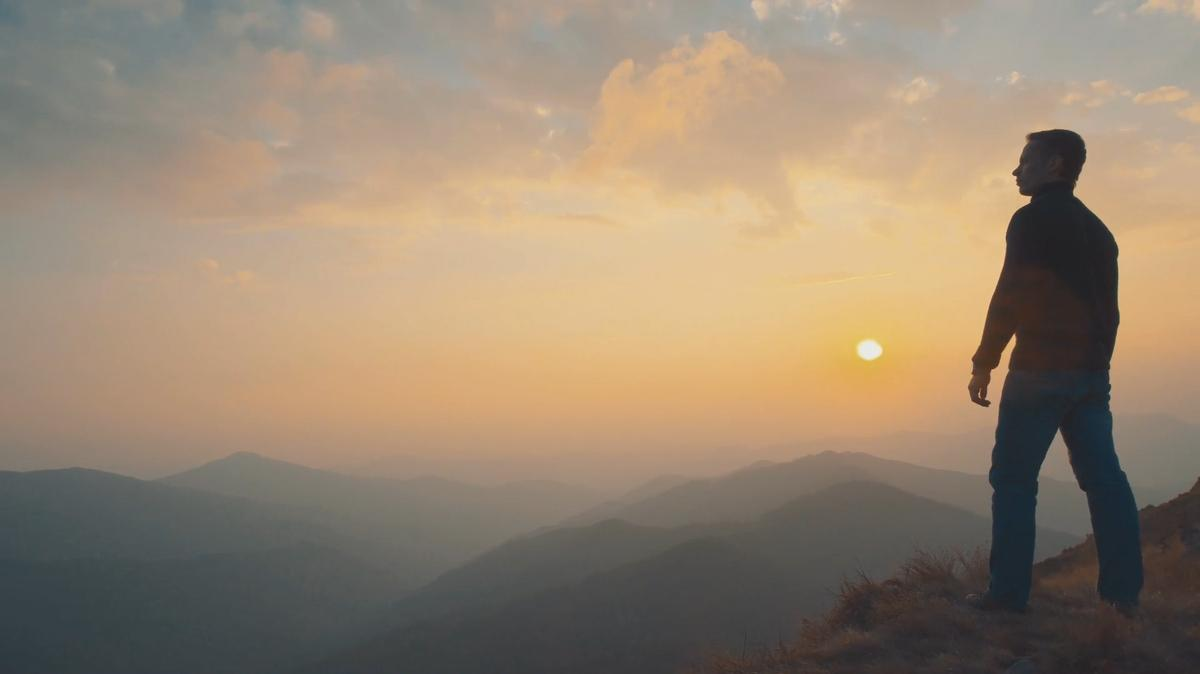 A man stands on top of a mountain overlooking a sunset.
