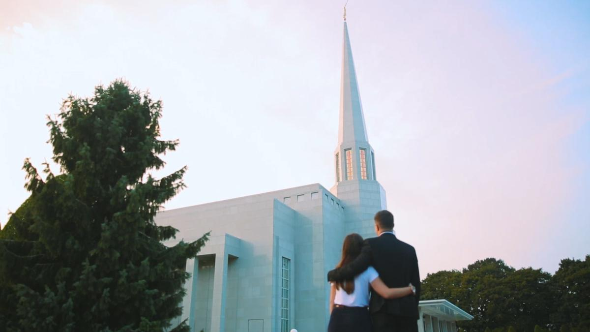 A young couple embrace as they look at the temple.