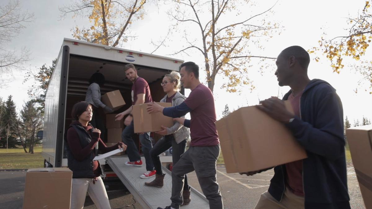 Young adults emptying a van full of boxes.