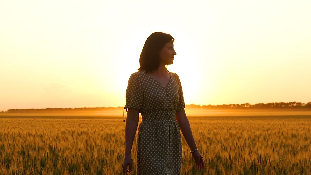 A woman walks in a hay field, an orange sunset behind her.