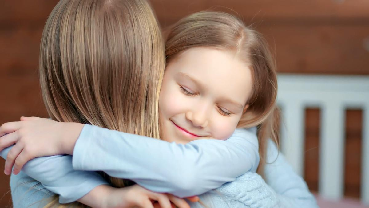 Two young blonde girls hug each other.