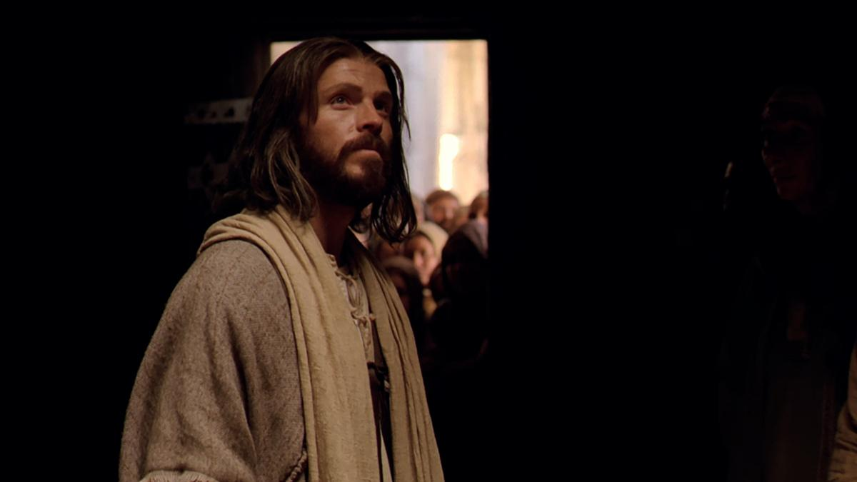 Jesus Christ (actor) looks up, smiling.