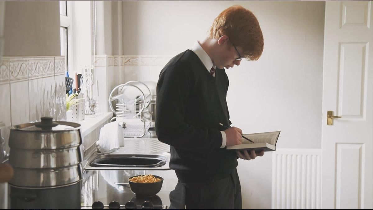 A young boy standing in the kitchen, leaning against the counter and studying the scriptures.