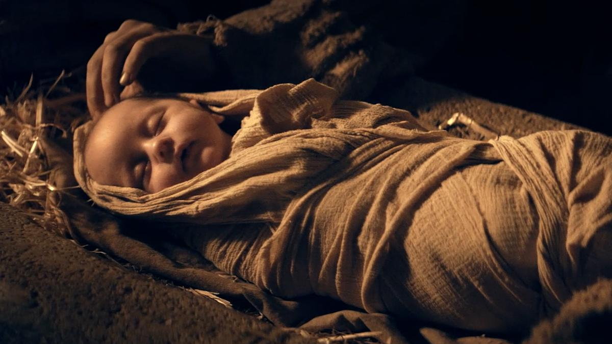 O menino Jesus dorme deitado numa manjedoura.
