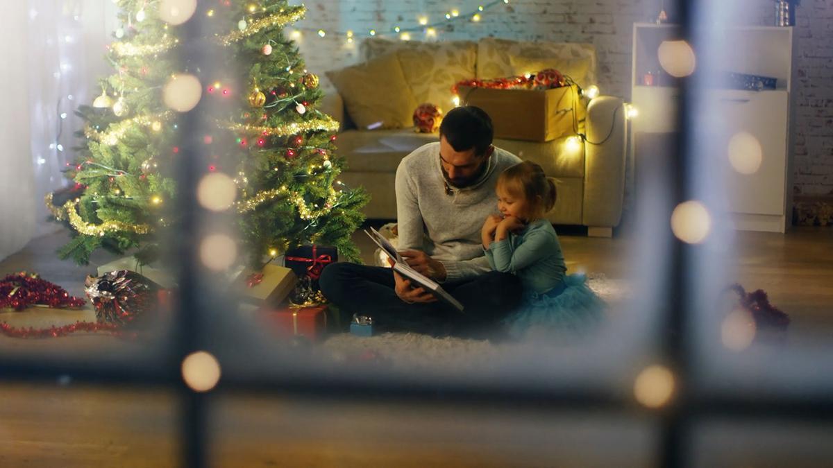 Pai e filha sentados a ler um livro, ao lado duma árvore de Natal