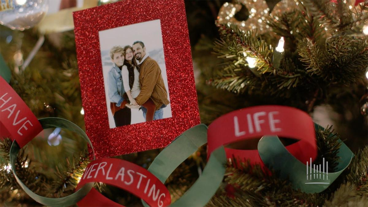 kuusen oksalla joulukoriste, jossa on perhekuva