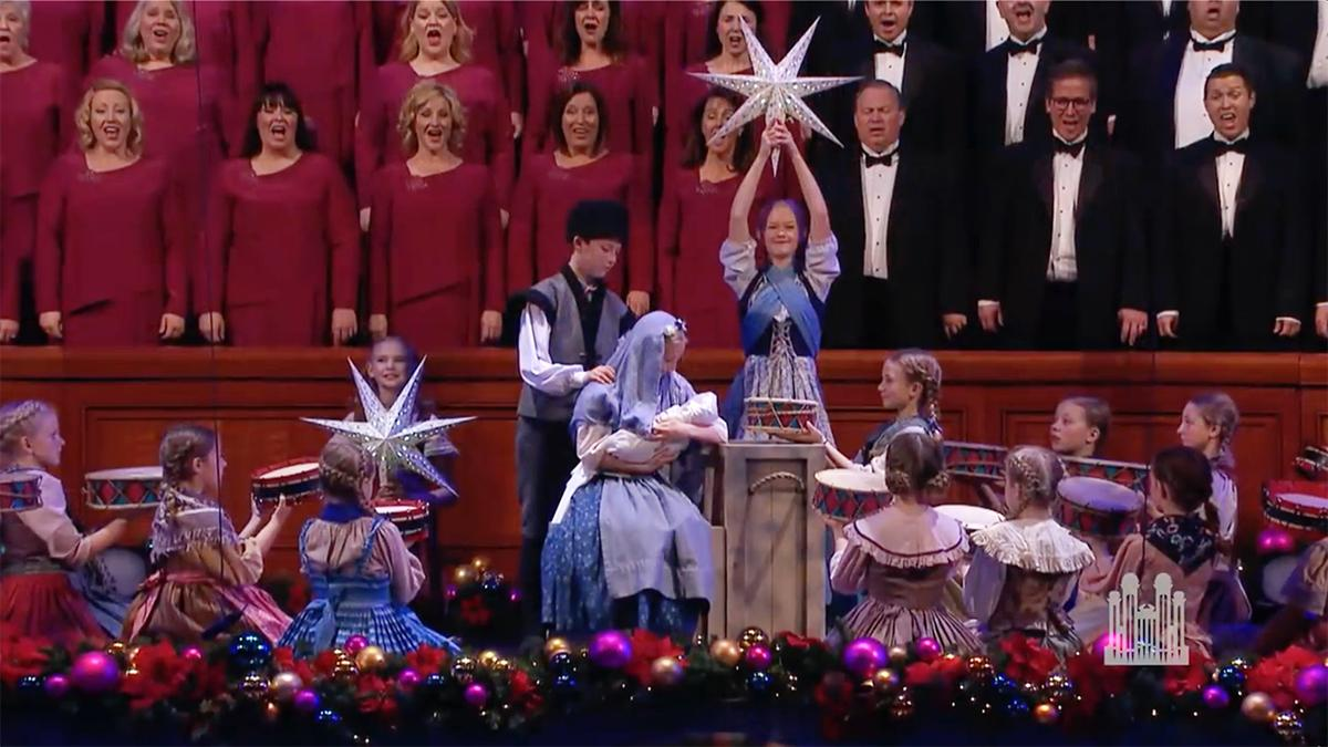 The Tabernacle Choir at Temple Square synger og barn viser en julekrybbe
