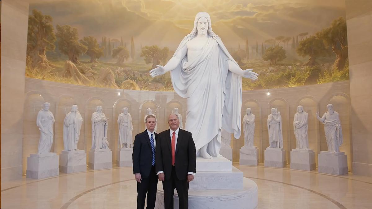 Két apostol áll Krisztus szobra előtt, a háttérben számos további fehér szoborral.