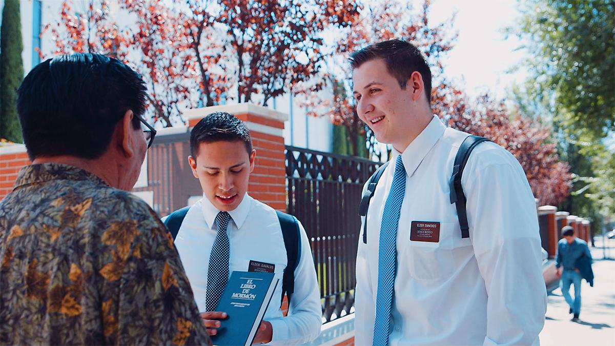 Two missionaries share the Book of Mormon with a man on the street.