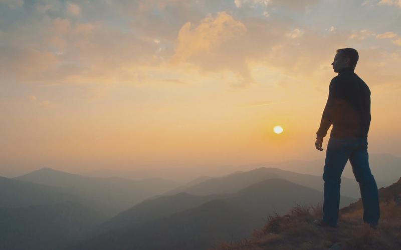 Neki moški stoji na vrhu gore in opazuje sončni zahod.