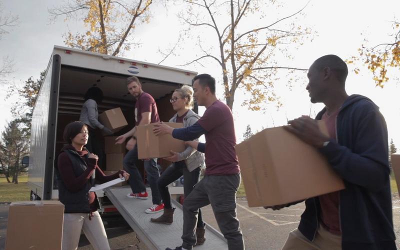Des jeunes adultes déchargeant la cargaison d'une camionnette.