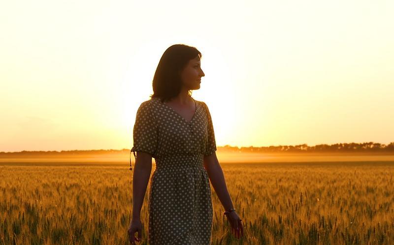 une femme marche dans un champ, devant un coucher de soleil orange