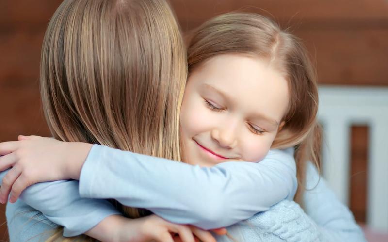 Deux jeunes filles blondes se prennent dans les bras.