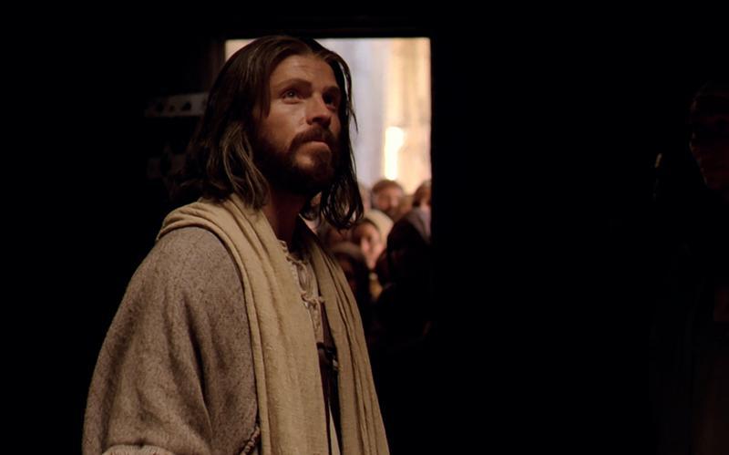 Jeesus Kristus (näyttelijä) katsoo ylös ja hymyilee.