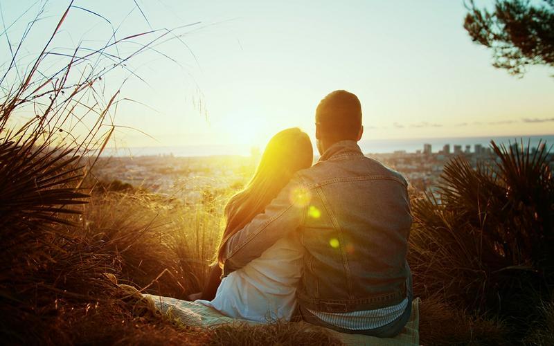 Млади пар седи на плажи при заласку сунца