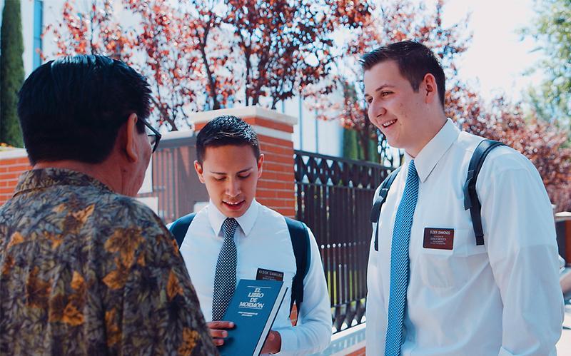 Dwóch misjonarzy pokazuje Księgę Mormona mężczyźnie na ulicy.