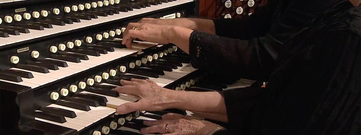 dos pares de manos tocando el órgano