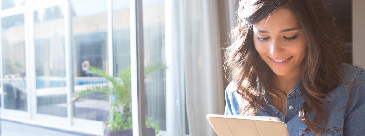 Eine Frau sitzt mit ihrem Tablet lächelnd am Fenster