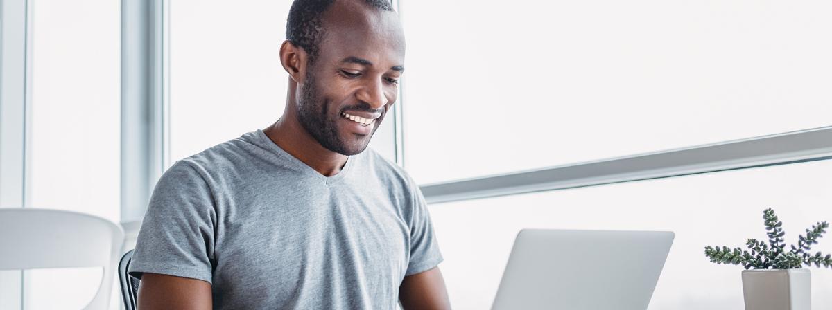 Muž sedí a usmívá se zatímco používá laptop.