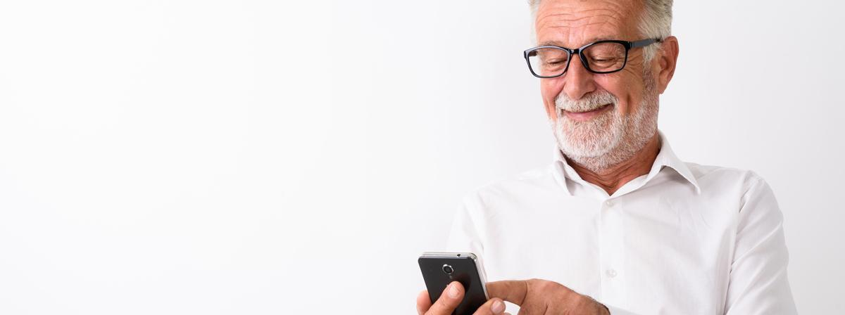 Насмејан старији човек стоји и користи мобилни телефон.