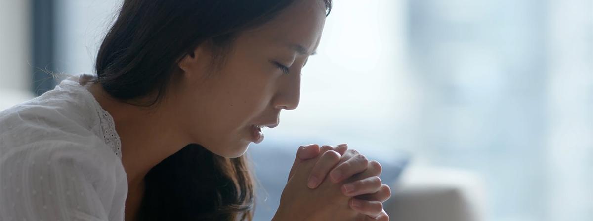 Eine junge Frau kniet im Gebet