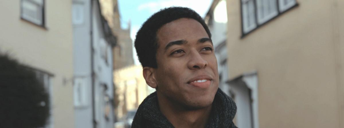 Un jeune homme sourit en levant les yeux.