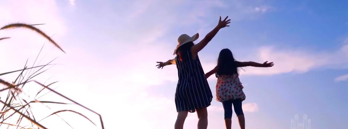 мајка и ћерка стоје раширених руку према небу