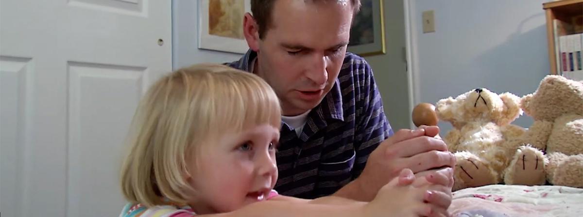 en far og datter knæler sammen i bøn