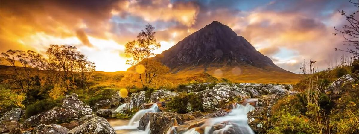 a hill and a stream in the sunset