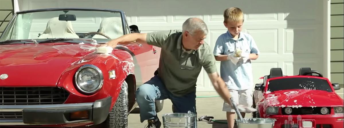 un abuelo y su nieto lavando sus coches juntos