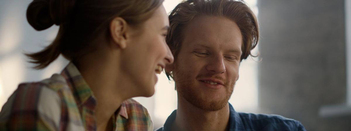 Një çift i ri duke buzëqeshur së bashku.