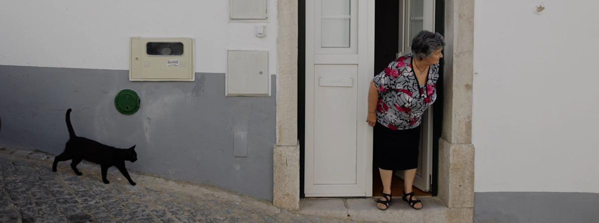 An old woman stands in her doorway looking confused.